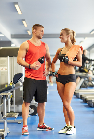 flirting: sport, fitness, lifestyle and people concept - smiling man and woman with protein shake bottle and towel talking in gym