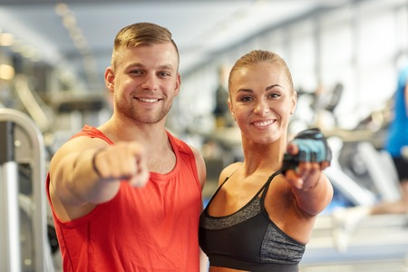 스포츠, 피트 니스, 라이프 스타일, 제스처 및 사람들이 개념 - 행복 한 남자와 여자의 체육관에서 손가락을 가리키는