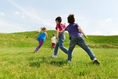 enfant qui joue: l'été, l'enfance, les loisirs et les gens concept - groupe d'enfants heureux de jouer tag jeu et en cours d'exécution sur le champ vert en plein air Banque d'images