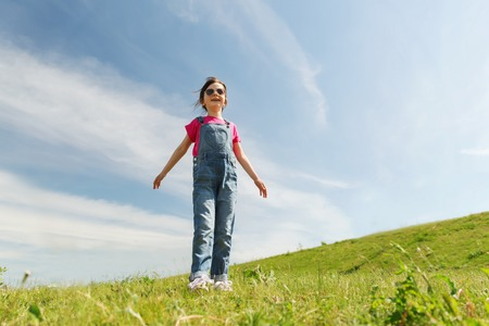 carelessness: summer, childhood, leisure and people concept - happy little girl over green field and blue sky outdoors Stock Photo