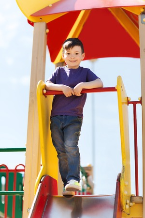 young boys: summer, childhood, leisure and people concept - happy little boy on children playground climbing frame Stock Photo