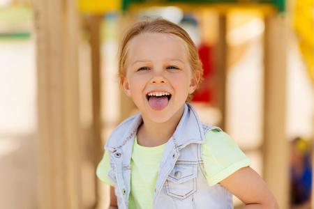 zomer, jeugd, vrije tijd en mensen concept - gelukkig meisje met tong en plezier op speelplaats Stockfoto