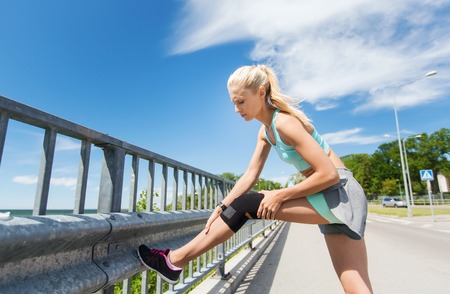 injured woman: fitness, sport, exercising and healthy lifestyle concept - young woman with injured knee or leg outdoors