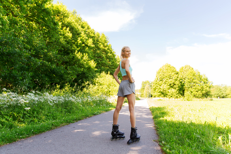 rollerblades: fitness, sport, summer, rollerblading and healthy lifestyle concept - happy young woman in rollerblades riding outdoors