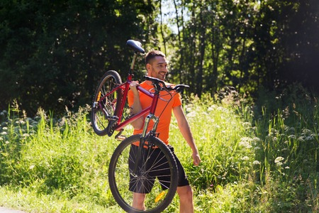 cycler: fitness, sport, people and healthy lifestyle concept - happy young man riding bicycle outdoors
