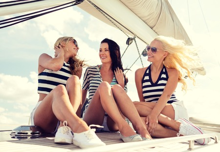 sail: vacation, travel, sea, friendship and people concept - smiling girlfriends sitting on yacht deck