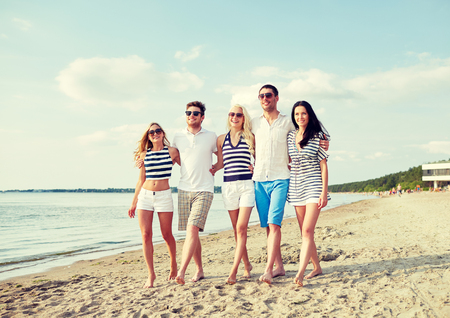 summer holidays: summer, holidays, sea, tourism and people concept - group of smiling friends in sunglasses walking on beach Stock Photo