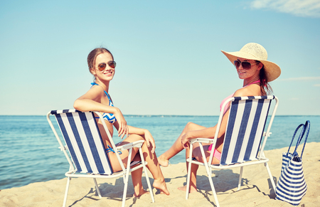 lounges: summer vacation, travel and people concept - happy women sunbathing in lounges on beach