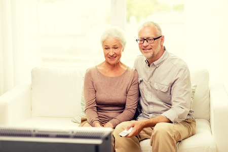 people watching: family, technology, age and people concept - happy senior couple watching tv at home