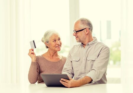 computer age: family, technology, age and people concept - happy senior couple with tablet pc computer and credit card at home