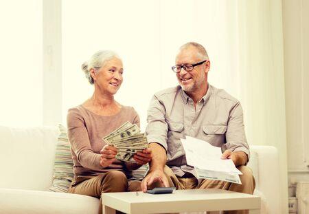 concepto de familia, negocios, ahorro, edad y personas - sonriente pareja senior con papeles, dinero y calculadora en casa