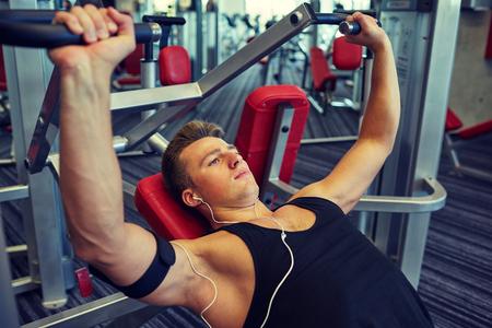 muscle training: Sport, Ausrüstung, Technologie, Lifestyle und Menschen Konzept - junger Mann mit Kopfhörern Brustmuskeln auf Fitnessgerät beugen