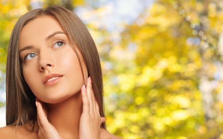 schoonheid, mensen en gezondheid concept - mooie jonge vrouw aan te raken haar nek over gele herfst achtergrond