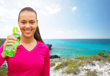 american sport: fitness, people and sport concept - smiling african american woman drinking from bottle over beach background