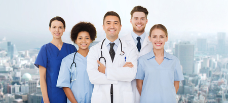multiracial: hospital, profession, people and medicine concept - group of happy doctors over city background Stock Photo