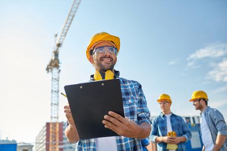 Geschäft, Gebäude, Papierkram und Menschen Konzept - glücklich builder in Helm mit Zwischenablage und Bleistift über Gruppe von Bauherren auf der Baustelle