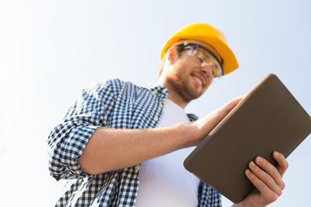 concept d'affaires, de bâtiment, d'industrie, de technologie et de personnes - gros plan de constructeur souriant en casque avec tablette pc à l'extérieur Banque d'images