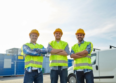industry, building, construction and people concept - happy male builders in high visible vests outdoors Foto de archivo