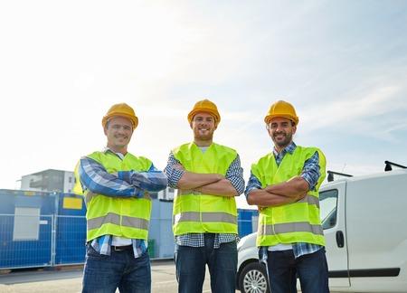 trabajadores: la industria, la construcción, la construcción y el concepto de la gente - constructores masculinos felices en altas chalecos visibles al aire libre