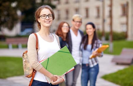 educação: educação, campus, amizade e conceito pessoas - grupo de estudantes adolescentes felizes com pastas escolares