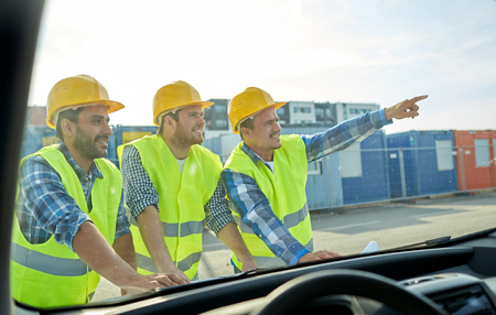 visible: building, construction, development, teamwork and people concept - close up of builders in hardhats and high visible vests with blueprint on car hood Stock Photo