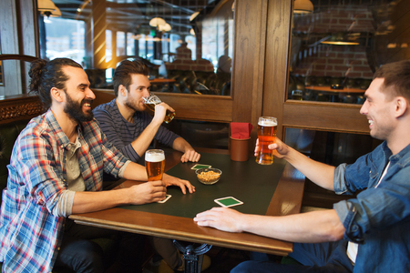 bachelor: people, leisure, friendship and and bachelor party concept - happy male friends drinking beer at bar or pub