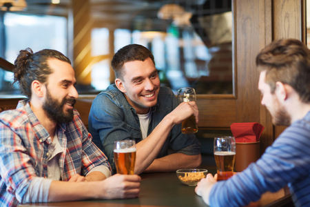 drinks on bar: people, men, leisure, friendship and communication concept - happy male friends drinking beer at bar or pub