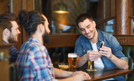 guys: people, men, leisure, friendship and technology concept - happy male friends with smartphone drinking beer at bar or pub