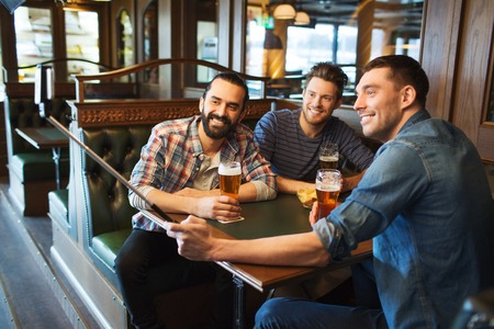 bachelor: people, leisure, friendship, technology and bachelor party concept - happy male friends drinking beer and taking picture with smartphone selfie stick at bar or pub Stock Photo