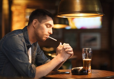 bad guy: people, smoking and bad habits concept - man drinking beer and lighting cigarette at bar or pub