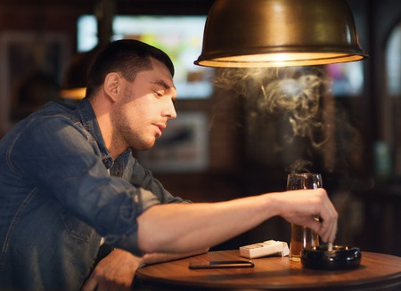 extinguishing: people, lifestyle and bad habits concept - man drinking beer and smoking and extinguishing his cigarette at bar or pub
