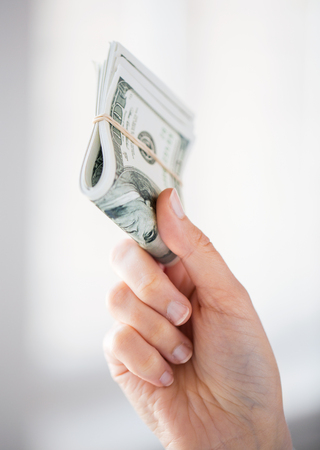 ahorros: negocios, las finanzas, el ahorro, la banca y la gente concepto - cerca de la mujer de las manos con nosotros la celebración de dinero en dólares Foto de archivo