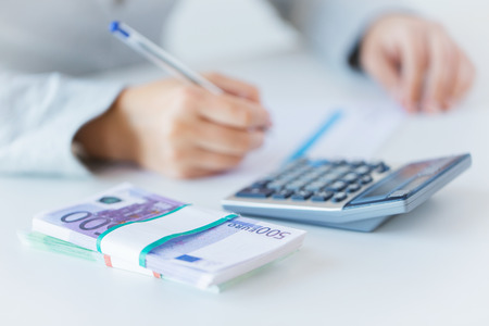 calculadora: business, finance, tax and people concept - close up of woman hands counting euro money with calculator and tax report form