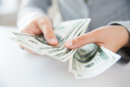 sales bank: business, finance, saving, banking and people concept - close up of woman hands counting us dollar money Stock Photo