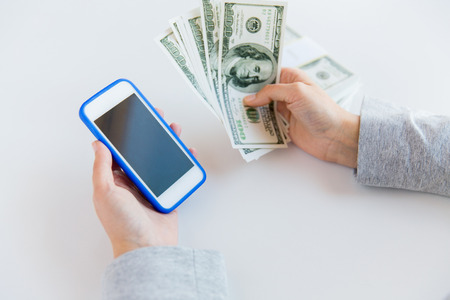 business finance: business, finance, saving, technology and people concept - close up of woman hands with smartphone and us dollar money