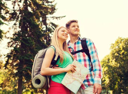 mochila de viaje: hiking, travel, vacation and friendship concept - smiling couple with map and backpack in nature