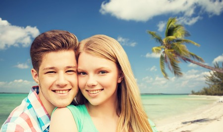 couples in love: holidays, vacation, love and people concept - smiling teenage couple hugging over tropical beach background