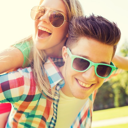 teen love: holidays, vacation, love and friendship concept - smiling teen couple in sunglasses having fun in summer park