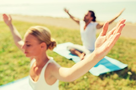 mats: fitness, sport, people and lifestyle concept - close up of couple making yoga exercises sitting with closed eyes on mats outdoors Stock Photo