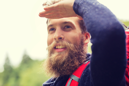 far away look: adventure, travel, tourism, hike and people concept - smiling man with beard and red backpack hiking