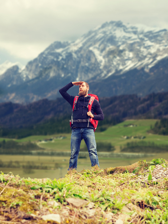 far away look: travel, tourism, hike and people concept - tourist with beard, backpack standing on edge of hill and looking far away over mountains background
