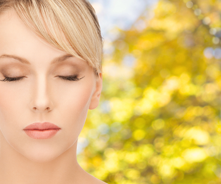 beauty, people and health concept - beautiful young woman face in make-up over yellow autumn background Stock fotó