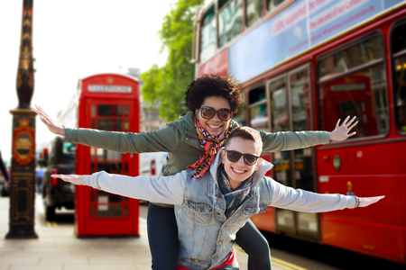 boys and girls: friendship, leisure, international, freedom and people concept - happy teenage couple in shades having fun over london city bus on street background Stock Photo