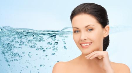 oxigeno: mujer joven y sonriente con los hombros descubiertos que toca su cara más de las salpicaduras de agua sobre fondo azul Foto de archivo