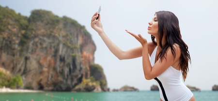 bali beach: sexy young woman taking selfie with smartphone and sending blow kiss over rock on bali beach background