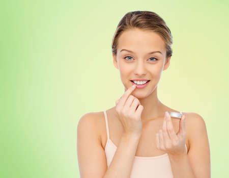 balm: smiling young woman applying lip balm to her lips over green natural background