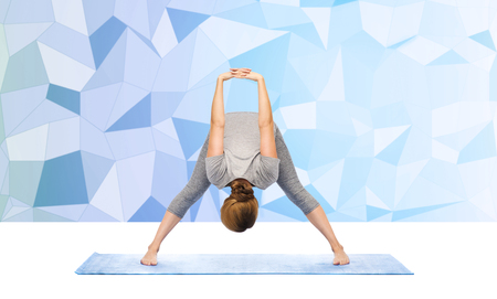 bends: fitness, sport, people and healthy lifestyle concept - woman making yoga in wide-legged forward bend pose on mat over blue polygonal background Stock Photo
