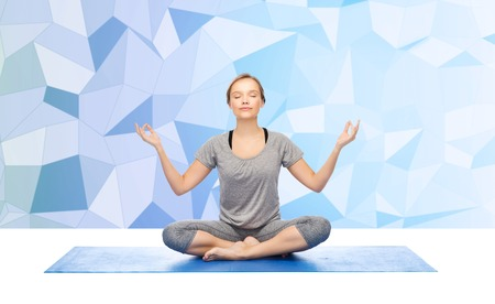 poses: fitness, sport, people and healthy lifestyle concept - woman making yoga meditation in lotus pose on mat over low poly background Stock Photo