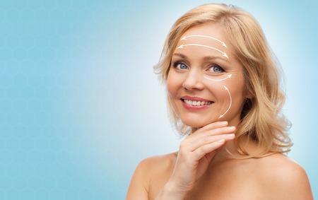 schoonheid, mensen, anti-aging en huidverzorging concept - lachende vrouw met blote schouders te raken gezicht over blauwe achtergrond