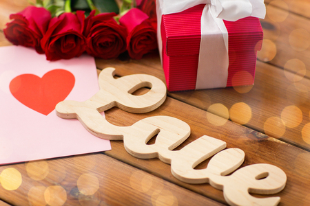 flirtation: close up of gift box, red roses and greeting card with heart on wood Stock Photo